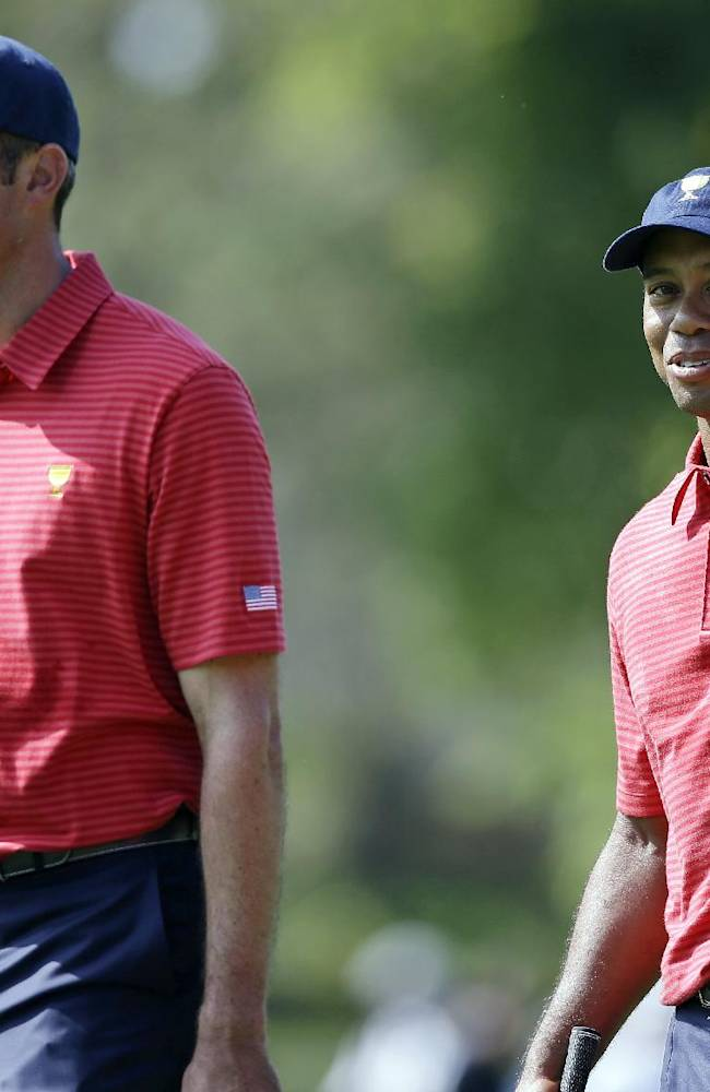 United States team player Tiger Woods, right, and team player Matt Kuchar walk up the 18th fairway during a practice round for the Presidents Cup golf tournament at Muirfield Village Golf Club Wednesday, Oct. 2, 2013, in Dublin, Ohio