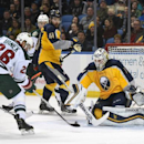 Minnesota Wild left winger Thomas Vanek (26), of Austria, shoots the puck against Buffalo Sabres goaltender Jhonas Enroth (1), of Sweden, as Sabres defenseman Andrej Meszaros (41), of Slovakia, looks on during the second period of an NHL hockey game Thurs