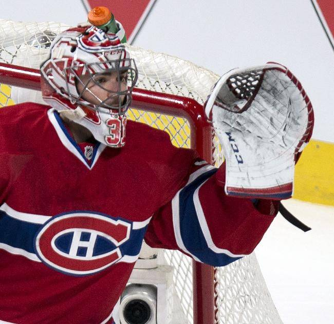 Montreal Canadiens goalie Carey Price gloves the puck as they face the Ottawa Senators during the first period of an NHL hockey game Saturday, March 15, 2014, in Montreal