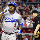 Los Angeles Dodgers' Juan Uribe gestures as he crosses home plate after hitting a solo home run against the Arizona Diamondbacks during the seventh inning of a baseball game on Sunday, April 13, 2014, in Phoenix The Associated Press