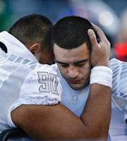 Oregon quarterback Marcus Mariota (8) is comforted by defensive tackle Ricky Havili-Heimuli (90), after Mariota was looked at by medical personnel after in the final minutes of an NCAA college football game against Arizona in Tucson, Ariz., Saturday, Nov 23, 2013. (AP Photo/The Oregonian, Thomas Boyd)
