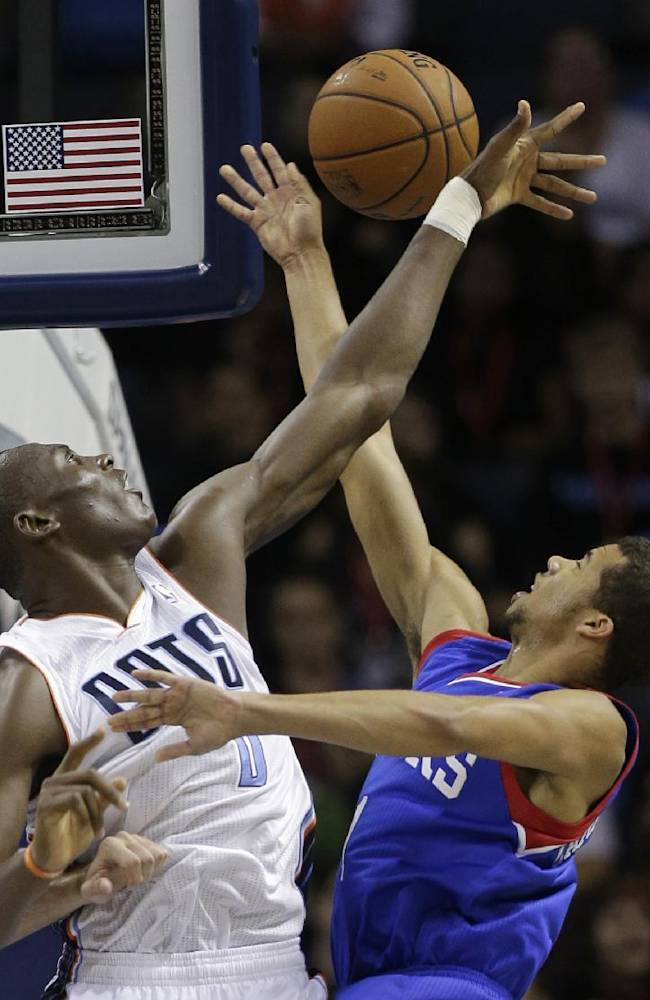 Charlotte Bobcats' Bismack Biyombo, left, blocks a shot by Philadelphia 76ers' Michael Carter-Williams, right, during the first half of a preseason NBA basketball game in Charlotte, N.C., Thursday, Oct. 17, 2013
