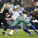 Dallas Cowboys defensive tackle Henry Melton (69) and teammate Jack Crawford (58) put pressure to New Orleans Saints quarterback Drew Brees (9) during the first half of an NFL football game Sunday, Sept. 28, 2014, in Arlington, Texas. The Associated Press