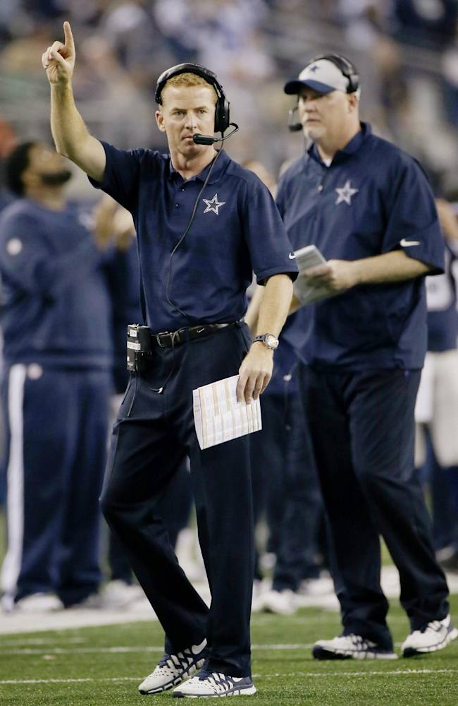 Dallas Cowboys head coach Jason Garrett signals from the field against the Oakland Raiders during the second half of an NFL football game, Thursday, Nov. 28, 2013, in Arlington, Texas