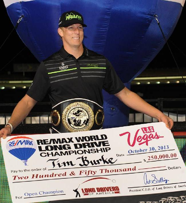 In this photo provided by the Las Vegas News Bureau, Tim Burke holds his oversized check after his winning drive of 427 yards during the Re/Max World Long Drive golf championship at Las Vegas Motor Speedway, Wednesday, Oct. 30, 2013