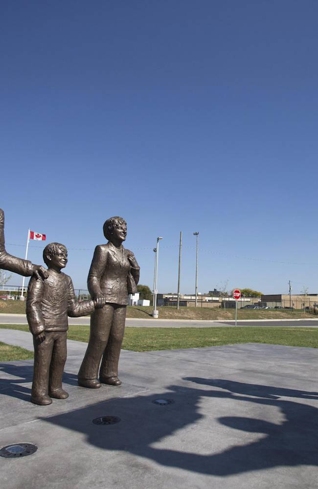 A woman stands near a statue of former NHL hockey player Wayne Gretzky and his parents Walter and Phyllis in front of the Wayne Gretzky Sports Centre in Gretzky's hometown of Brantford, Ontario on Wednesday, Oct. 2, 2013. The statues, since cleaned, were defaced with blue paint by vandals overnight Monday