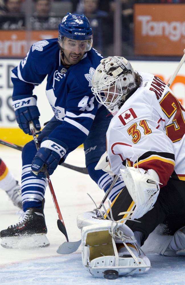Calgary Flames goaltender Karri Ramo makes a save on Toronto Maple Leafs center Nazem Kadri during second period NHL action in Toronto on Tuesday April 1, 2014