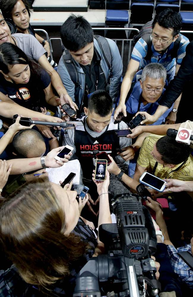 The Houston Rockets' Jeremy Lin is interviewed by a horde of reporters during a break in his team's practice at the Mall of Asia Arena at suburban Pasay city, south of Manila, Philippines, Tuesday Oct. 8, 2013. Lin has easily stolen the spotlight as the Houston Rockets practice for this week's first ever NBA preseason game against the Indiana Pacers in the basketball-obsessed Philippines