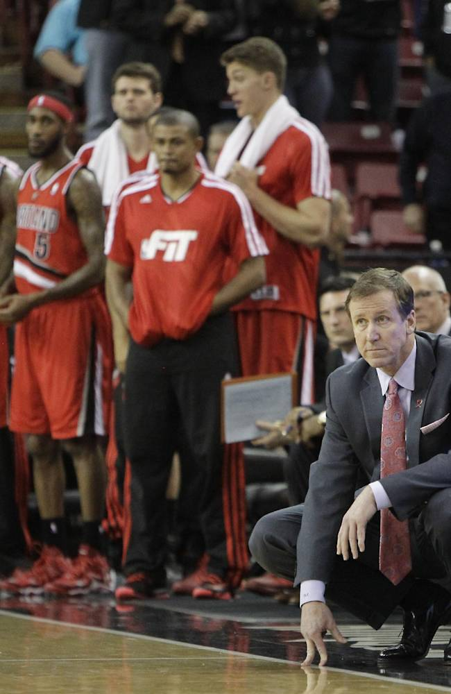 Portland Trail Blazers head coach Terry Stotts, kneeling right, watches the closing moments of the Trail Blazers 123-119 loss to the Sacramento Kings in an NBA basketball game in Sacramento, Calif., Tuesday, Jan. 7, 2014