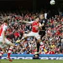 Arsenal's Hector Bellerin, center, jumps for the ball with Hull City's Michael Dawson, right, during the English Premier League soccer match between Arsenal and Hull City at the Emirates stadium in London Saturday, Oct.18, 2014