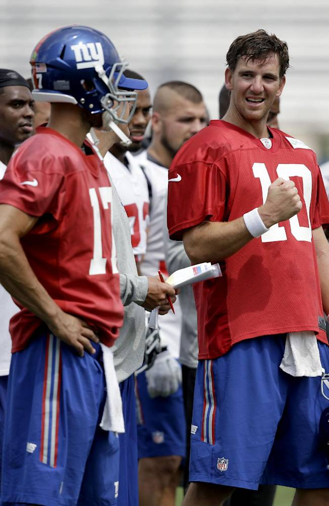 New York Giants quarterback Eli Manning (10) talks on the sidelines during NFL football training camp in East Rutherford, N.J., Tuesday, July 22, 2014