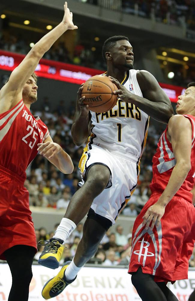 Indiana Pacers' Lance Stephenson, center, prepares to pass the ball to a team mate as Houston Rockets' Jeremy Lin, right, and Chandler Parsons defend during their NBA  pre-season game dubbed NBA Global Games Thursday Oct. 10, 2013, at the Mall of Asia Arena at suburban Pasay city, south of Manila, Philippines. The Rockets won 116-96, in the first NBA game in this basketball-crazy Southeast Asian nation which is part of the NBA's global schedule that will have eight teams play in six countries this month