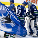 Vancouver Canucks left wing Daniel Sedin (22) celebrates his team's win with goalie Joe Cannata (34) after an NHL preseason hockey game against the San Jose Sharks in Vancouver, British Columbia, Tuesday, Sept. 23, 2014. The Associated Press