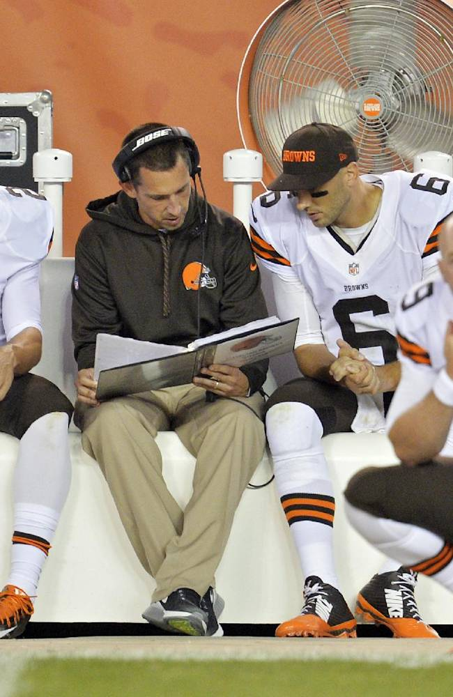 In this Aug. 23, 2014, file photo, Cleveland Browns quarterbacks Johnny Manziel (2) listens in as offensive coordinator Kyle Shanahan, center, talks with Brian Hoyer (6) on the sidelines in the fourth quarter of a preseason NFL football game against the St. Louis Rams in Cleveland. Manziel doesn't view himself as the Browns' savior, but almost everyone else does. The dynamic rookie quarterback will begin the season as Cleveland's second-string quarterback, but it may not be long before he's moved ahead of Hoyer, who already seems to be looking over his shoulder