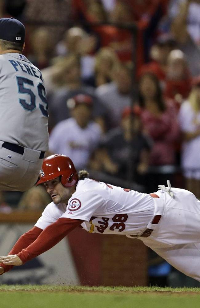 St. Louis Cardinals' Pete Kozma, right, scores the game-winning run on a passed ball as Seattle Mariners relief pitcher Oliver Perez covers home during the 10th inning of a baseball game Friday, Sept. 13, 2013, in St. Louis. The Cardinals won 2-1