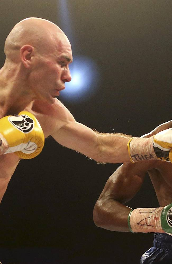 Britain's Stuart Hall, left, lands a punch to South Africa's Vusi Malinga during their IBF bantamweight title fight at the First Direct Arena, in Leeds, England, Saturday Dec. 21, 2013. Hall claimed the vacant IBF bantamweight title on Sunday after a points win over Malinga