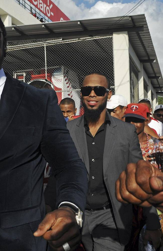 Dominican Republic baseball players Hanley Ramirez, left, and Jose Reyes, center, are greeted by fans upon their arrival to the Quisqueya Stadium to attend the 2013 World Baseball Classic victory celebration in Santo Domingo, Dominican Republic, Thursday, Nov. 28, 2013. The Dominican Republic team won the third edition of the World Baseball Classic in March, finishing unbeaten in eight games