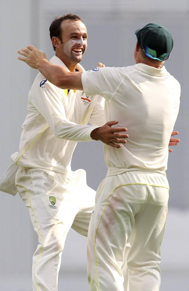 Australia's Nathan Lyon, left, celebrates with teammate David Warner after getting the wicket of England's Matt Prior on the fourth day of their series-opening Ashes cricket test match at the Gabba in Brisbane, Australia, Sunday, Nov. 24, 2013