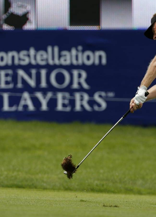 Bernhard Langer of Germany hits his approach shot to 18th green during the second round of the Senior Players Championship golf tournament at Fox Chapel Golf Club in Pittsburgh, Friday, June 27, 2014