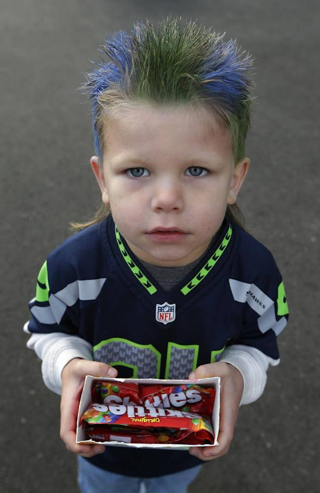Seattle Seahawks fan Oskar Van De Plasch, 4, poses for a photo as he carries an offering of the Skittles candy favored by Seattle Seahawks running back Marshawn Lynch as he waits at the Seahawks' headquarters in Renton, Wash., Sunday, Jan. 26, 2014, to see players and coaches board buses for their flight to play the Denver Broncos in the NFL Super Bowl XLVIII football game in East Rutherford, N.J