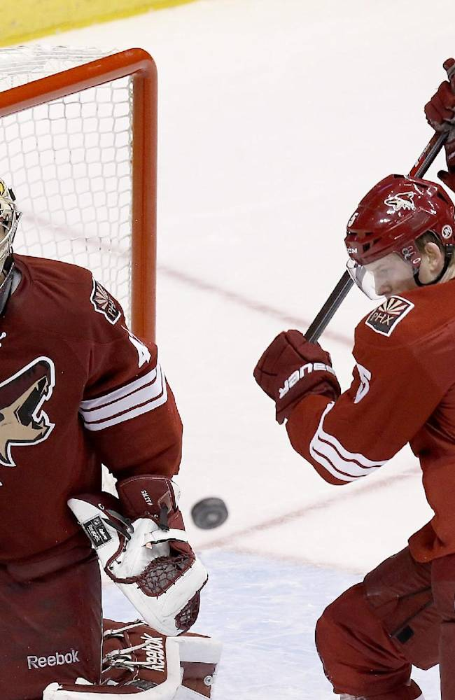 Phoenix Coyotes' Mike Smith, left, and Connor Murphy (5) and Columbus Blue Jackets' Brandon Dubinsky (17) watch the puck fly through the air during the third period of an NHL hockey game Thursday, Jan. 2, 2014, in Glendale, Ariz. The Blue Jackets defeated the Coyotes 2-0