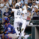Seattle Mariners' Robinson Cano (22) leaps with Kyle Seager as Cano heads into the dugout after a home run, while Texas Rangers catcher Robinson Chirinos waits for the next batter in the first inning of a baseball game Tuesday, Aug. 26, 2014, in Seattle. (AP Photo/Elaine Thompson)