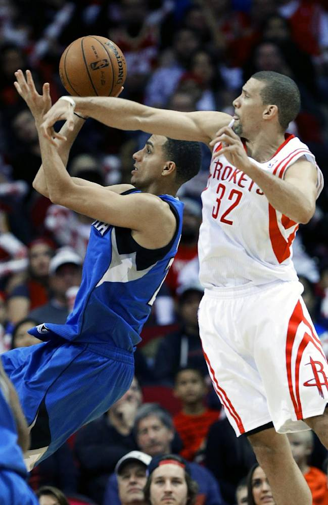 Minnesota Timberwolves' Kevin Martin, left, shoots as Houston Rockets' Francisco Garcia (32) tries to knock the ball away in the second half of an NBA basketball game Saturday, Nov. 23, 2013, in Houston. The Rockets won 112-101