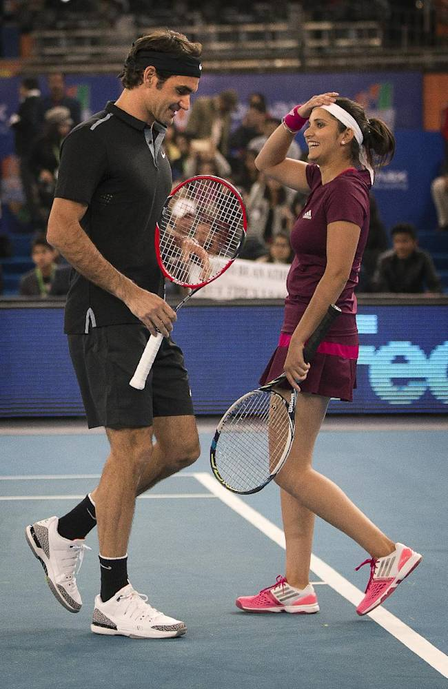 Micromax Indian Aces players Roger Federer, left, talks to Sania Mirza after scoring a point against  DBS Singapore Slammers's Bruno Soares and Daniela Hantuchova in the mixed doubles match,  during the International Premier Tennis League, in New Delhi, India, Sunday, Dec. 7, 2014. (AP Photo /Manish Swarup)