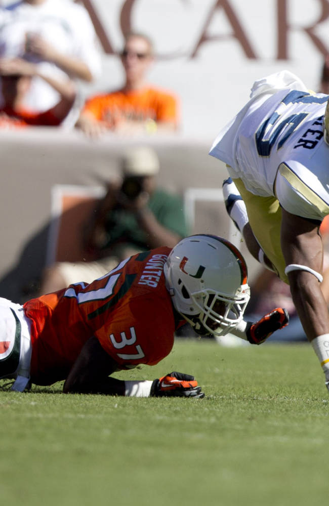 Miami's Ladrius Gunther, left, tackles Georgia Tech's DeAndre Smelter during the first half of an NCAA college football game in Miami Gardens, Fla., Saturday, Oct. 5, 2013