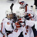 Washington Capitals center Nicklas Backstrom (19) is congratulated by teammates after his shootout goal on Detroit Red Wings goalie Jimmy Howard in an NHL hockey game in Detroit, Friday, Nov. 15, 2013. The Capitals won 4-3 The Associated Press