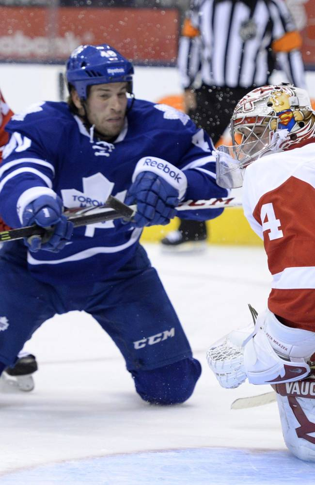 Detroit Red Wings goalie Petr Mrazek, right, makes a save as Toronto Maple Leafs' Troy Bodie, center, looks for a rebound and Red Wings' Xavier Ouellet defends during second-period preseason NHL hockey game action in Toronto, Saturday Sept. 28, 2013