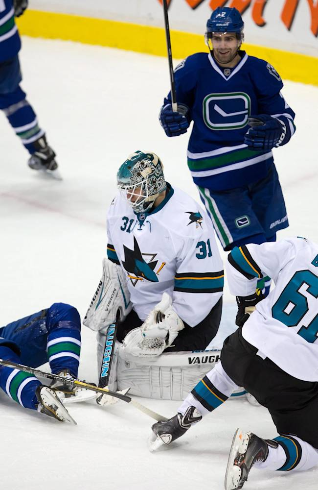 Vancouver Canucks' Daniel Sedin, left, of Sweden, and Dan Hamhuis, top, celebrate a goal by teammate Kevin Bieksa as San Jose Sharks' goalie Antti Niemi, centre, of Finland, and Justin Braun, right, look on during second period NHL hockey action in Vancouver, British Columbia, on Thursday Nov. 14, 2013