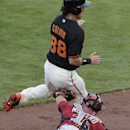 Arizona Diamondbacks catcher Miguel Montero, bottom, tags but drops the ball against San Francisco Giants' Tyler Colvin who scores off a single hit by Hector Sanchez during the fifth inning of a spring training baseball game on Sunday, March 2, 2014, in S