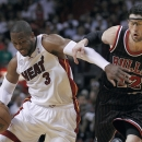 Miami Heat's Dwayne Wade (L) moves against Chicago Bulls' Kirk Hinrich in the first half of their NBA basketball game in Miami, Florida April 14, 2013. REUTERS/Andrew Innerarity (UNITED STATES - Tags: SPORT BASKETBALL)