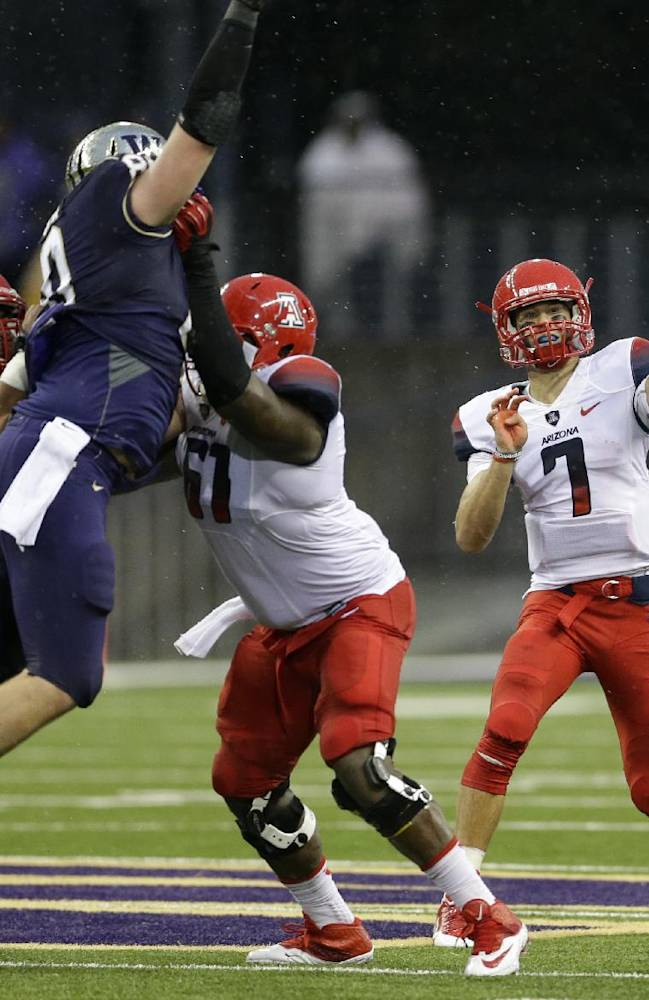 Arizona quarterback B.J. Denker (7) passes in the second half against Washington during an NCAA college football game, Saturday, Sept. 28, 2013, in Seattle. At left, Arizona's Steven Gurrola, left, and Cayman Bundage, third from right, block Washington's Evan Hudson, second from left. Washington beat Arizona, 31-13