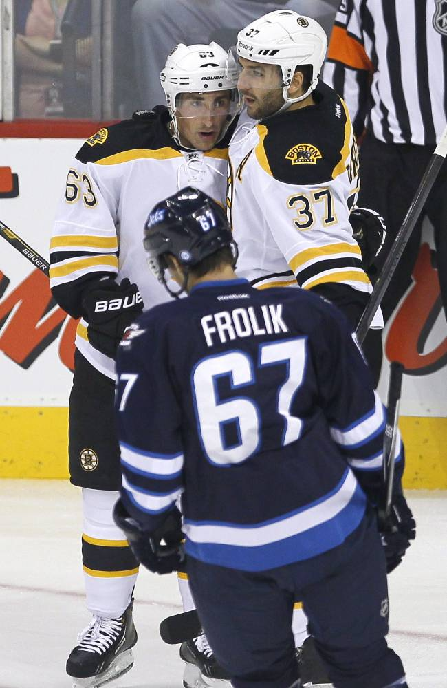 Boston Bruins' Brad Marchand (63) and Patrice Bergeron (37) celebrate Bergeron's goal as Winnipeg Jets' Michael Frolik skates past during the first period of a preseason NHL hockey game Thursday, Sept. 26, 2013, in Winnipeg, Manitoba