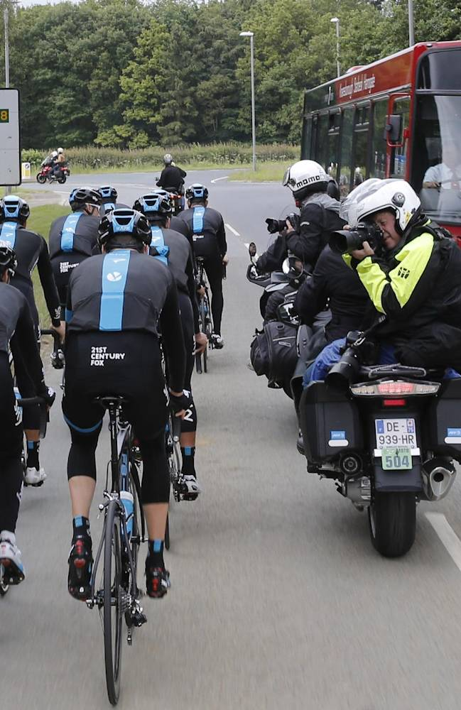 Photographer riding on the back of motorcycles takes pictures of Britain's Christopher Froome, rear right, and his Sky teammates during a training ahead of the Tour de France cycling race in Leeds, Britain, Thursday, July 3, 2014. The Tour de France will start on Saturday July 5th in Leeds, and finishes in Paris on Sunday July 27th
