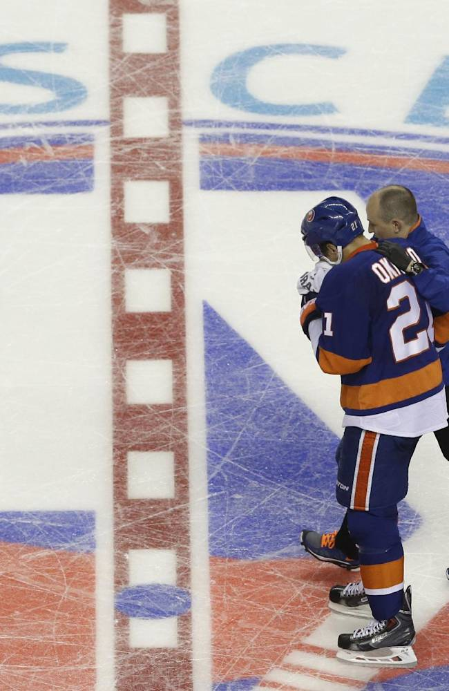 New York Islanders right wing Kyle Okposo leaves the ice with a trainer during the third period of a preseason NHL hockey game against the New Jersey Devils, Saturday, Sept. 21, 2013, in New York. The Devils won 3-0