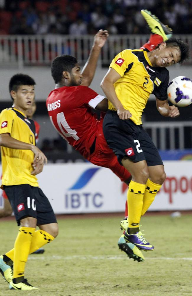 Muhammad Afi Aminuddin of Brunei, right, and Hariss Harun of Singapore, center, fight for the ball during their soccer match at the 27th SEA Games in Naypyitaw, Myanmar, Friday, Dec. 13, 2013. Singapore beat Brunei 2-0