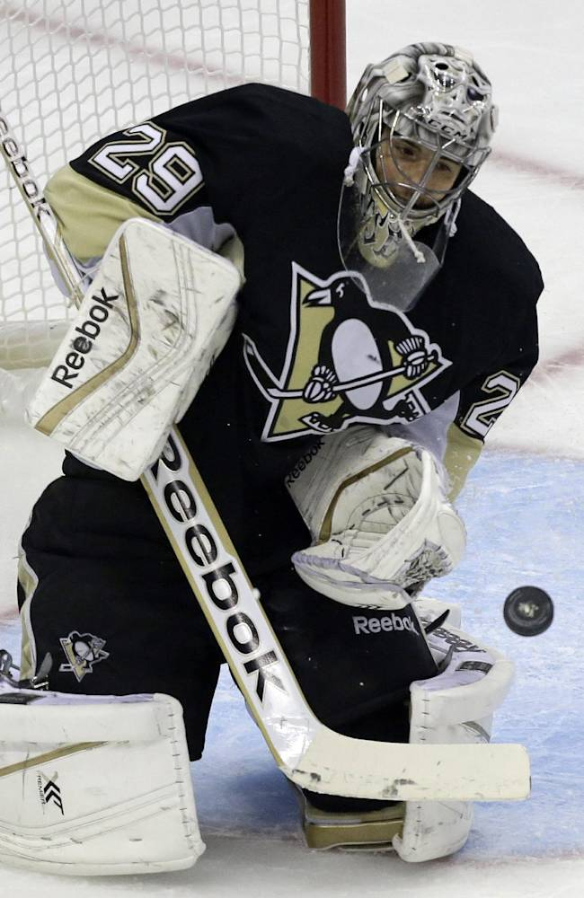 Pittsburgh Penguins goalie Marc-Andre Fleury (29) blocks a shot in the first period of an NHL hockey game against the Vancouver Canucks in Pittsburgh Saturday, Oct. 19, 2013. The Penguins won 4-3 in shootout