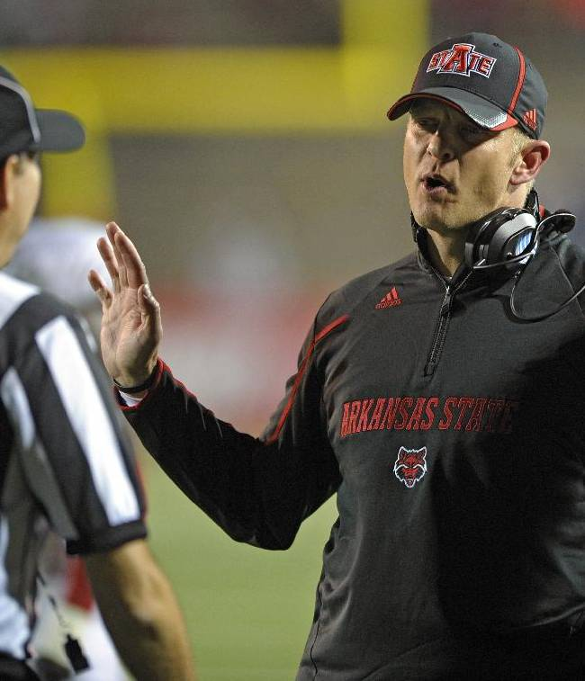 In this Nov. 2, 2013 file photo, Arkansas State head coach Bryan Harsin talks with linesman Scott Peterson during a timeout with South Alabama in the second quarter of an NCAA college football game in Mobile, Ala. A person familiar with the decision tells The Associated Press that Boise State has hired  Harsin as its next coach. The person spoke on condition of anonymity because the move had not become official