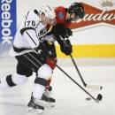 Los Angeles Kings' Tanner Pearson, left, battles Calgary Flames' Ben Hanowski for the puck during the first period of an NHL hockey game in Calgary, Alberta, Monday, March 10, 2014. (AP Photo/The Canadian Press, Jeff McIntosh)
