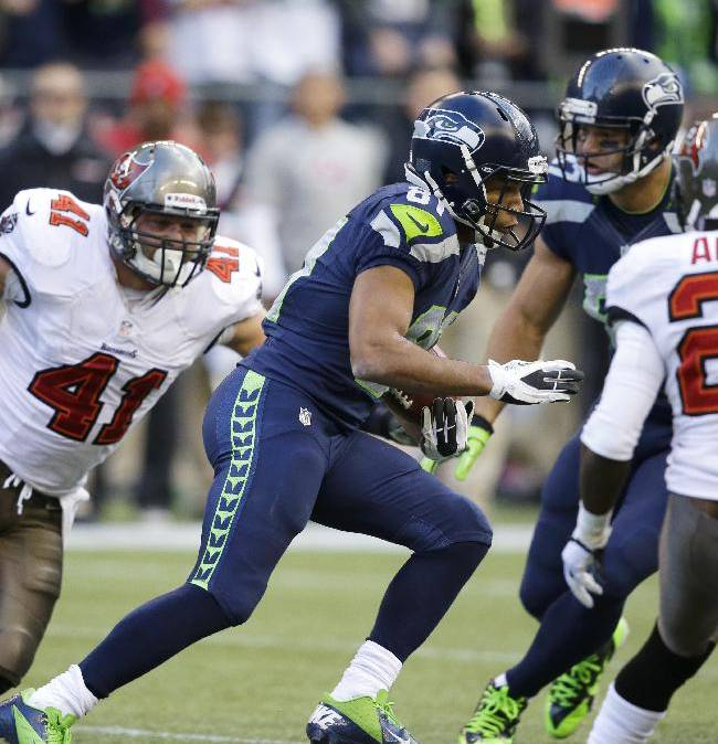 Seattle Seahawks put returner Golden Tate (81) avoids Tampa Bay Buccaneers' Erik Lorig (41) and Michael Adams (21) as he makes a 71-yard punt return in the second half of an NFL football game, Sunday, Nov. 3, 2013, in Seattle