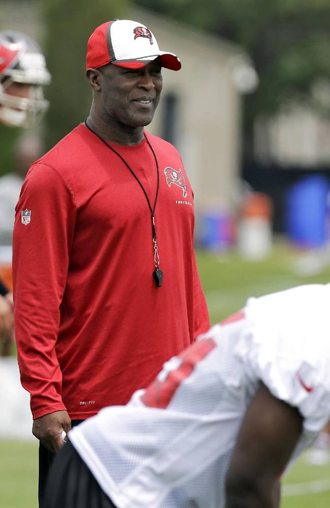 New Tampa Bay Buccaneers head coach Lovie Smith, center, stands during voluntary NFL minicamp football practice Tuesday, April 22, 2014, in Tampa, Fla