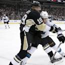 San Jose Sharks' Ben Smith (21) checks Pittsburgh Penguins' Beau Bennett (19) off the puck in the corner during the second period of an NHL hockey game in Pittsburgh Sunday, March 29, 2015. (AP Photo/Gene J. Puskar)