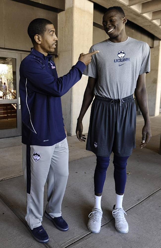 Connecticut NCAA college basketball head coach Kevin Ollie, left, talks with player Amida Brimah prior to the annual Husky Run, Wednesday, Sept. 25, 2013, in  Storrs, Conn