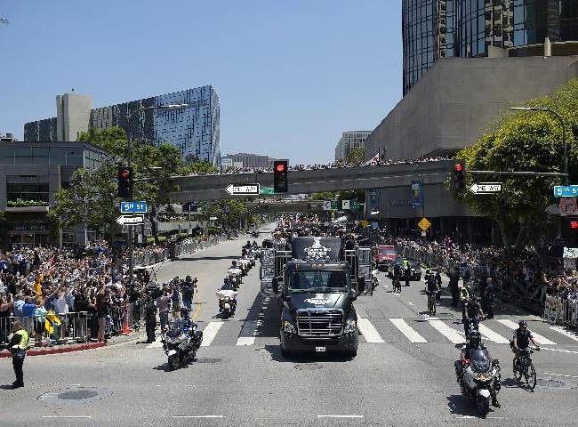 Members of the Los Angeles Kings NHL hockey team hold up the Stanley Cup trophy while riding in a parade through downtown Los Angeles, Monday, June 16, 2014. The parade and rally were held to celebrate the Kings' second Stanley Cup championship in three seasons. The Kings defeated the New York Rangers for the title