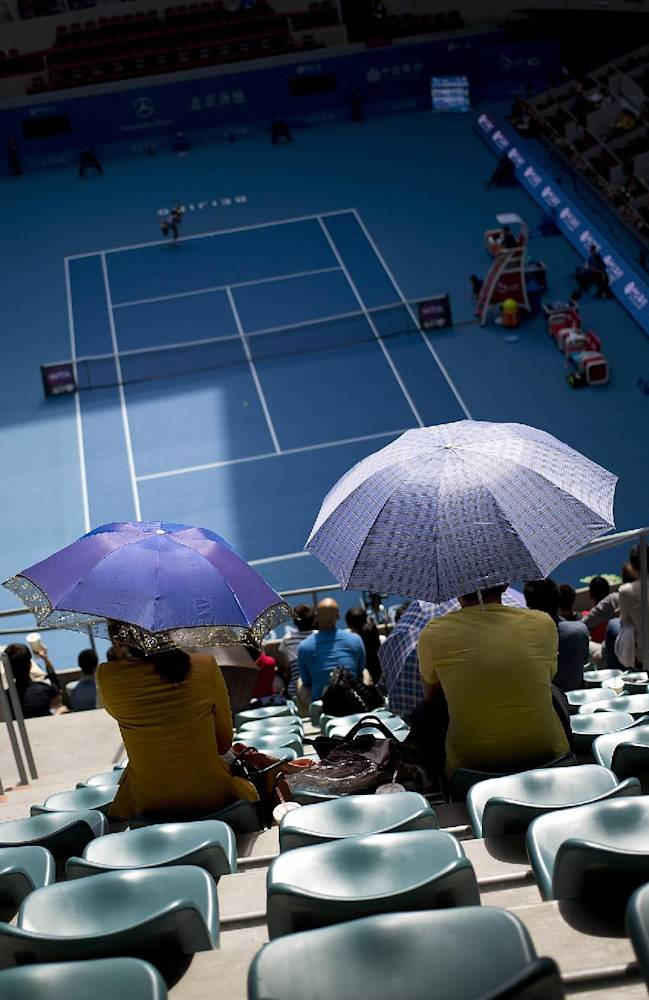 Spectators hold umbrellas to shield from the sun as they watch a match between Serena Williams of the U.S. and Francesca Schiavone of Italy at the China Open tennis tournament at the National Tennis Stadium in Beijing, China Tuesday, Oct. 1, 2013