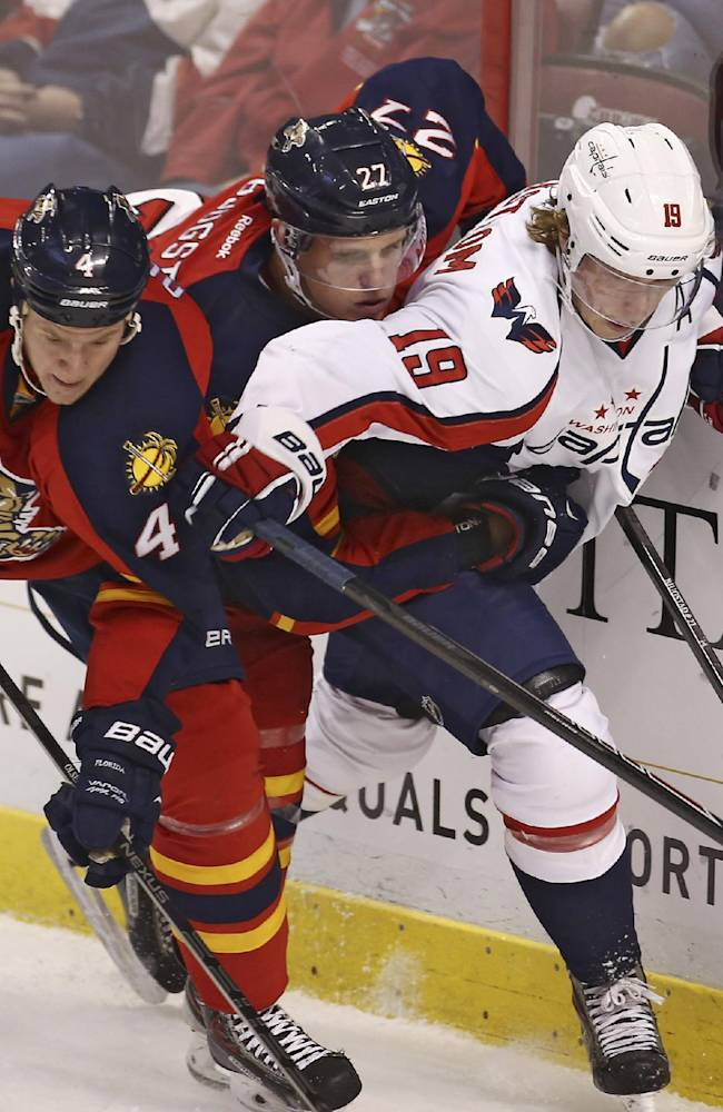 Florida Panthers players Dylan Olsen (4) and Nick Bjugstad (27) apply pressure to Washington Captials' Troy Backstrom (19) during the first period of a NHL hockey game in Sunrise, Fla., Friday, Dec. 13, 2013
