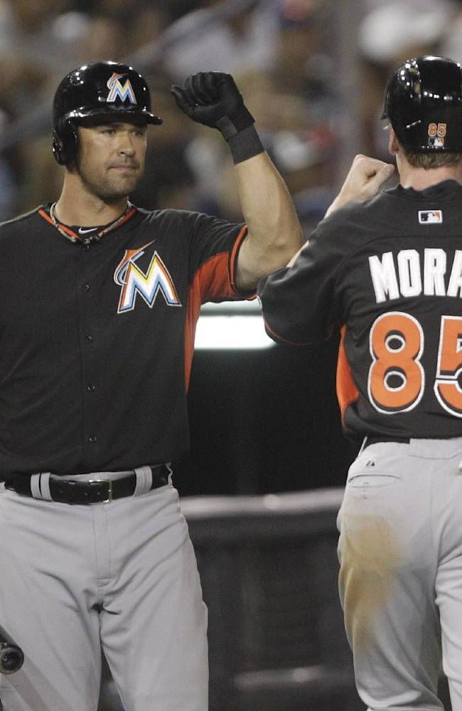 Miami Marlins Colin Moran, right, celebrates with teammate Garrett Jones after Moran scored during the sixth inning of an exhibition baseball game the